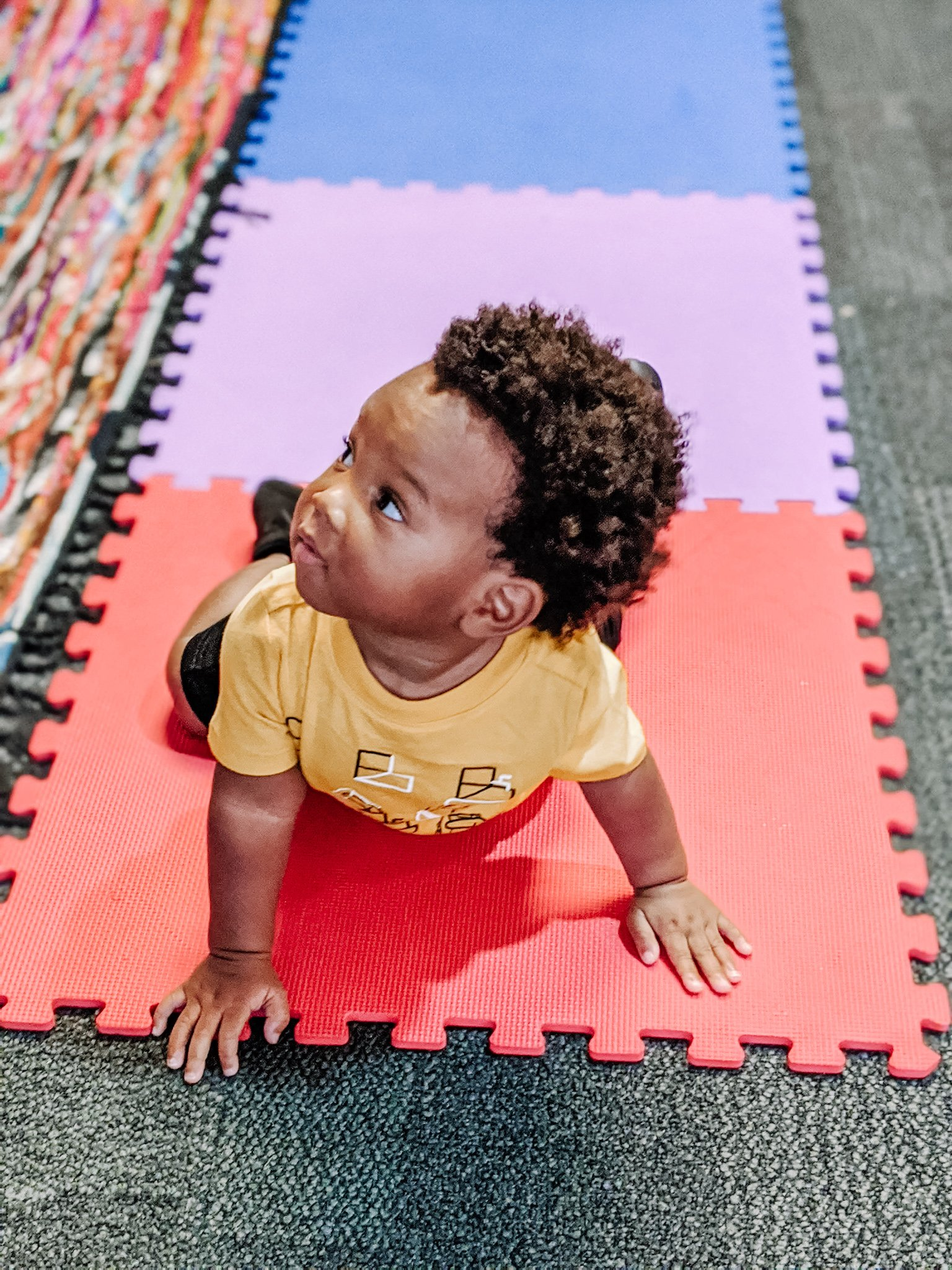 baby crawling on mat at museum