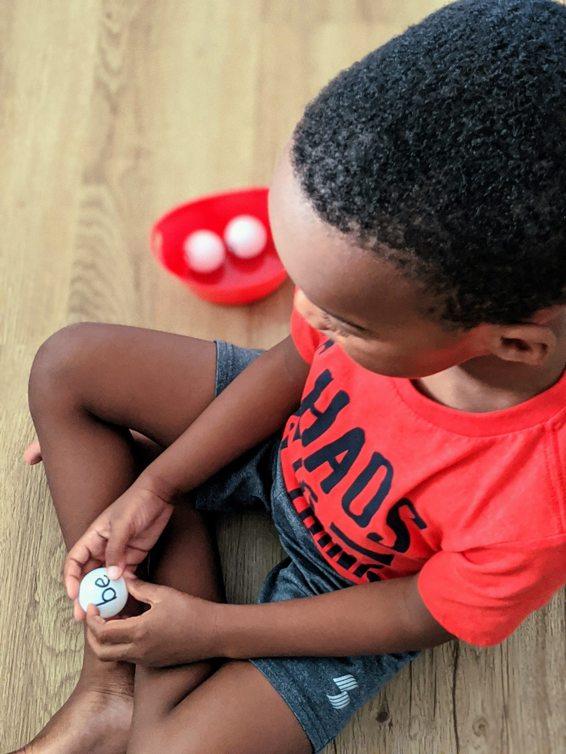 Black boy holding table tennis balls for sight words activity