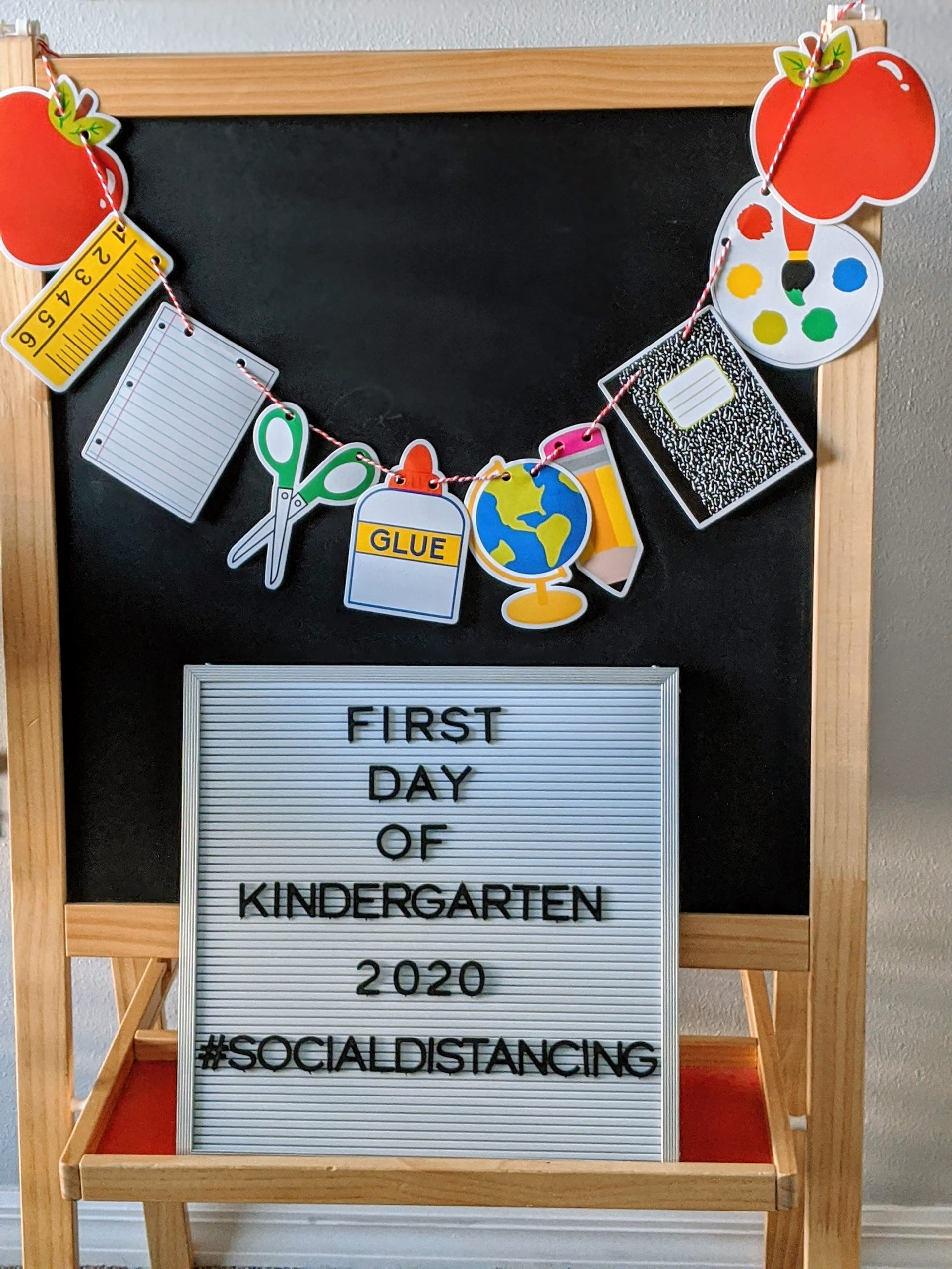 chalkboard with back to school banner and letter board with first day of school information
