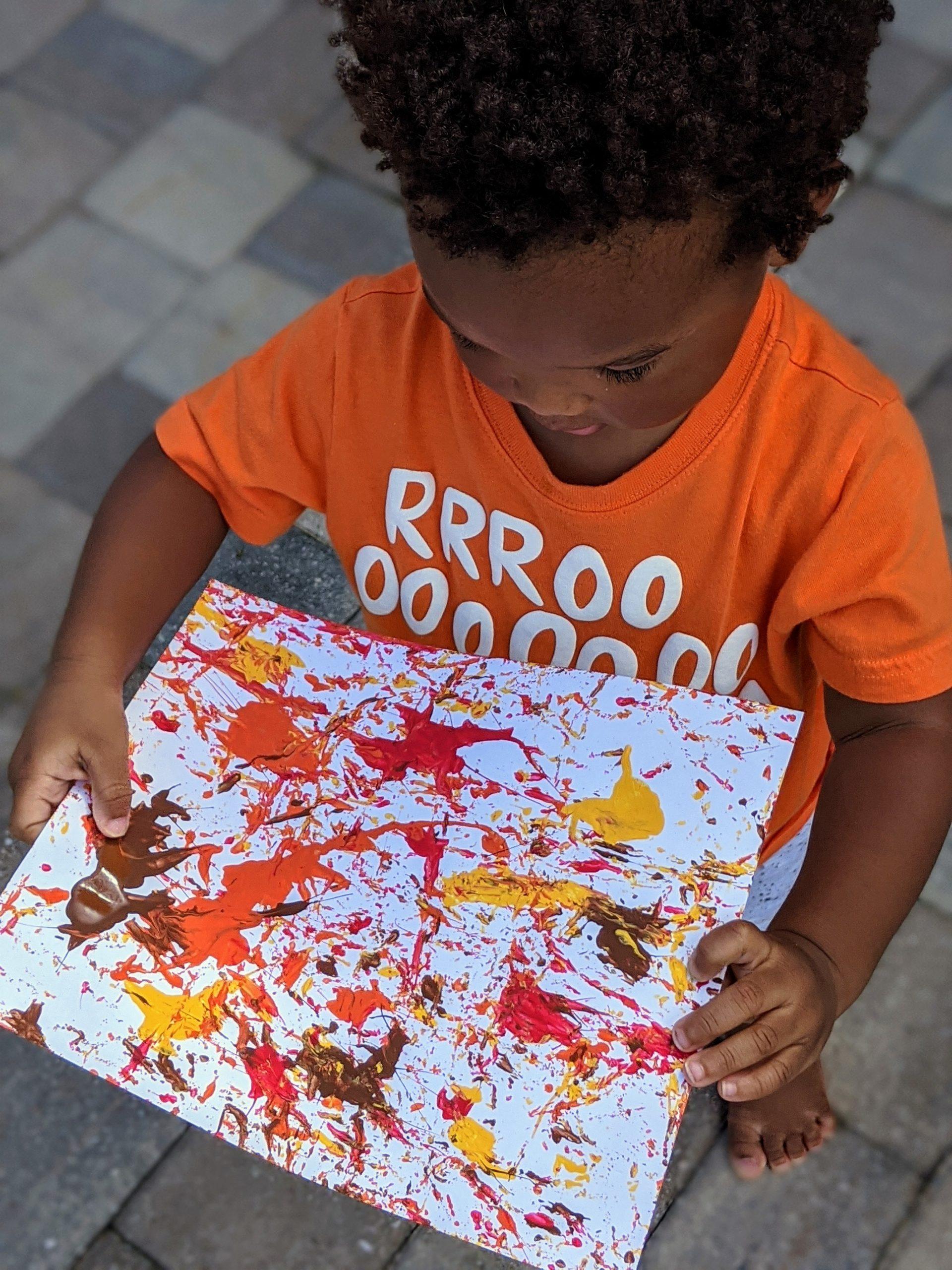 toddler holding acorn paint artwork