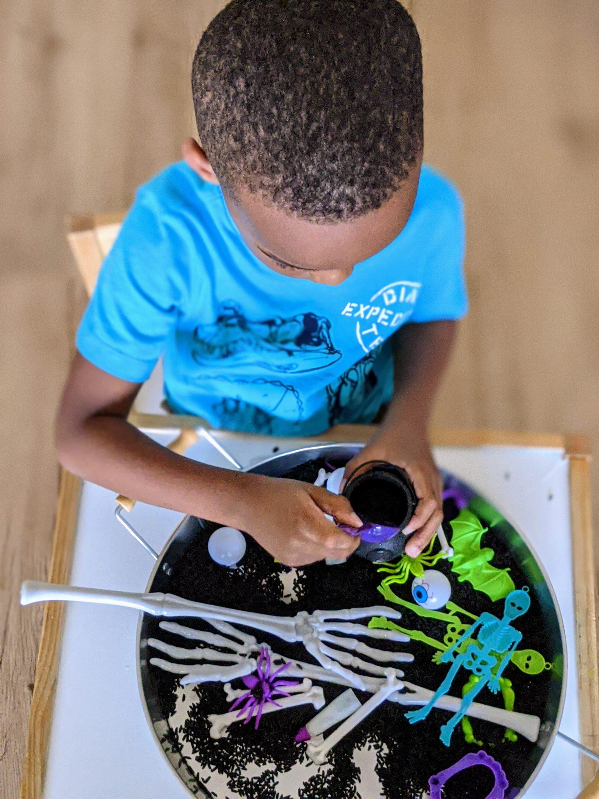 Black boy playing with sensory tray