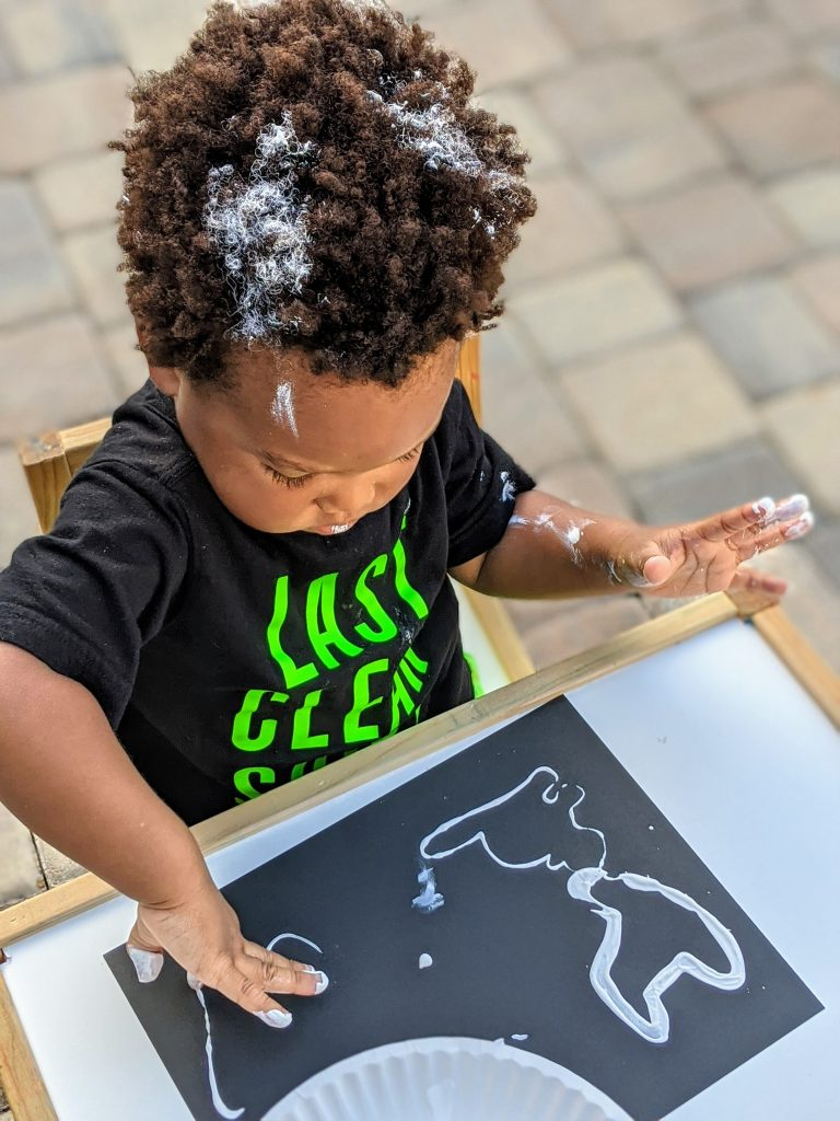 Black toddler painting with cookie cutters for Halloween