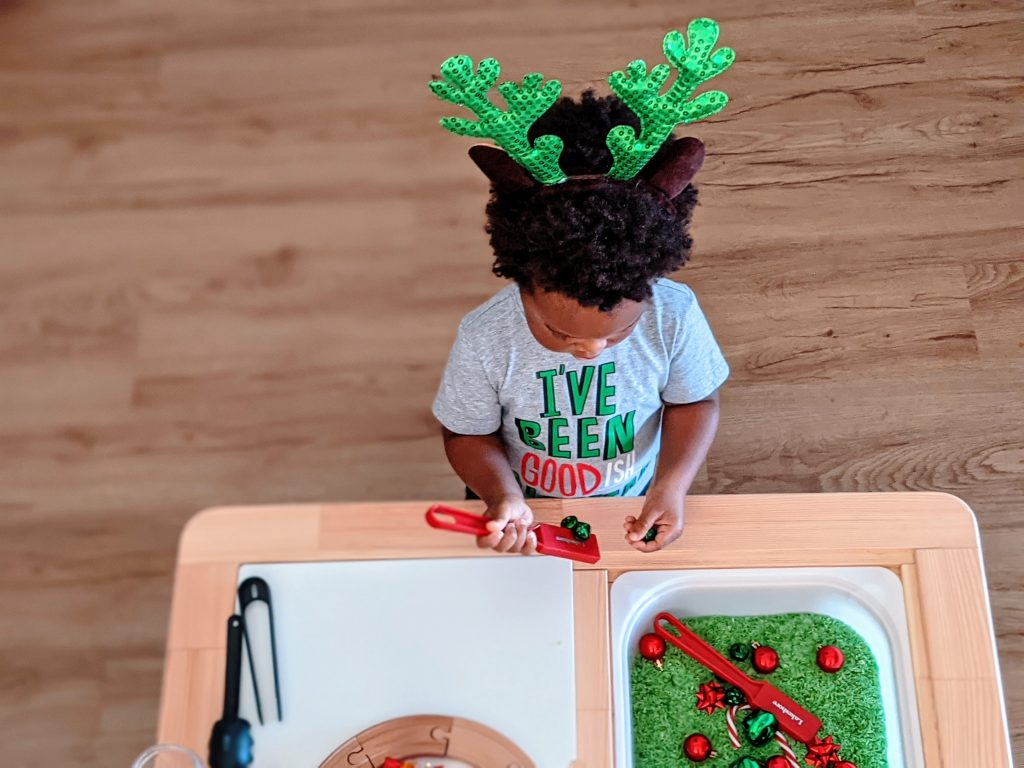 toddler playing with holiday sensory bin