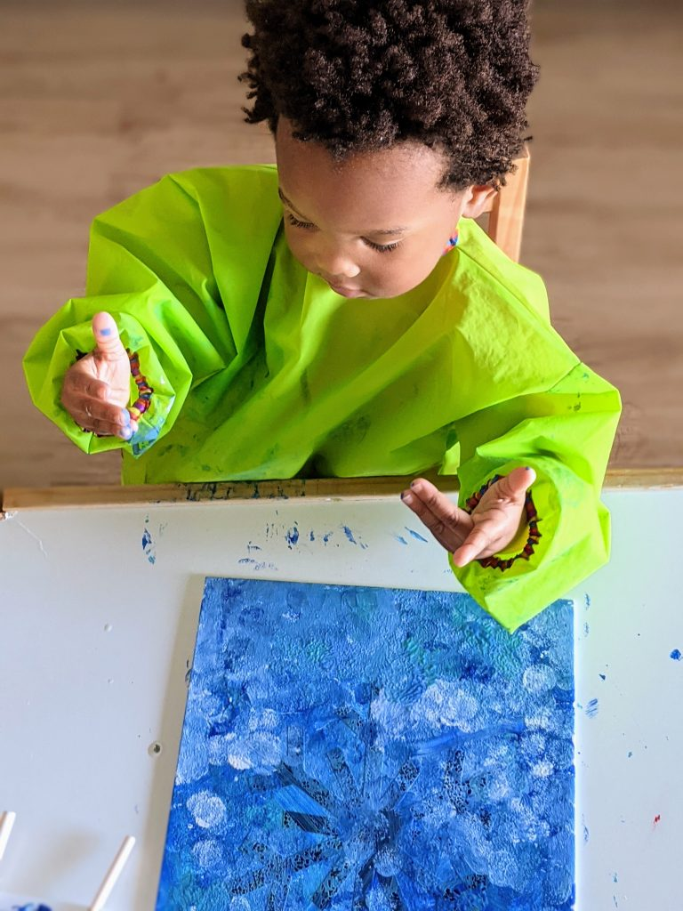 toddler sitting at an IKEA children's table and painting