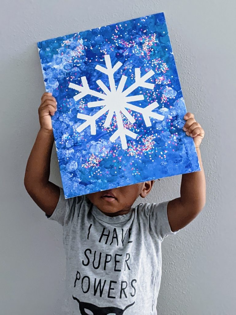 toddler holding his snowflake art project