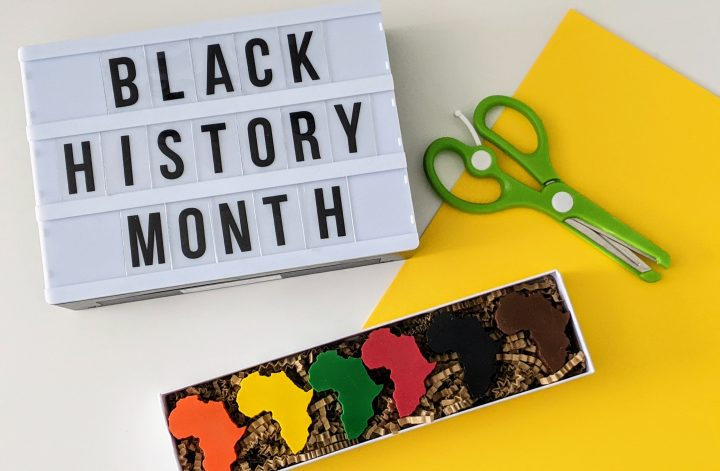 Black History Month crafts featured image with sign, scissors, yellow paper and Africa shaped crayons